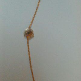 Bracelet estampe fleur doré et petite perle incrustée à l'intérieur